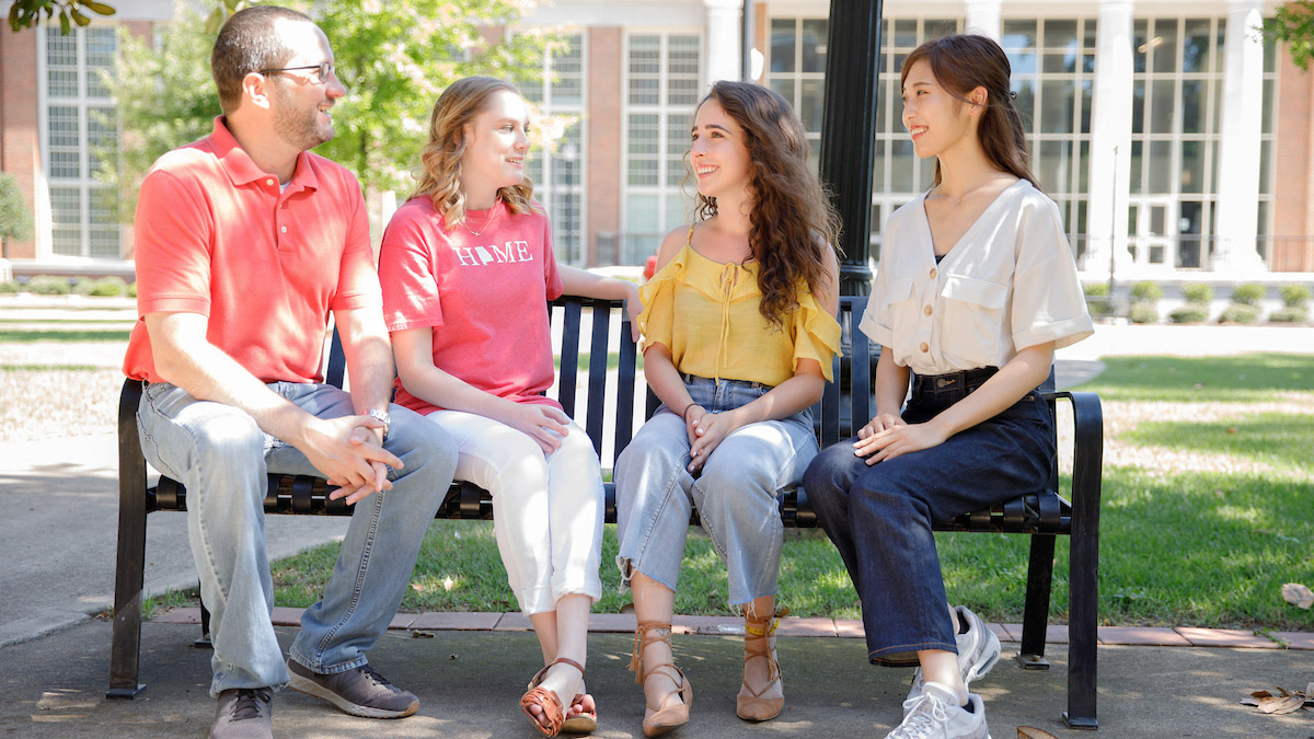 Students talking on a bench on the Crimson Promenade