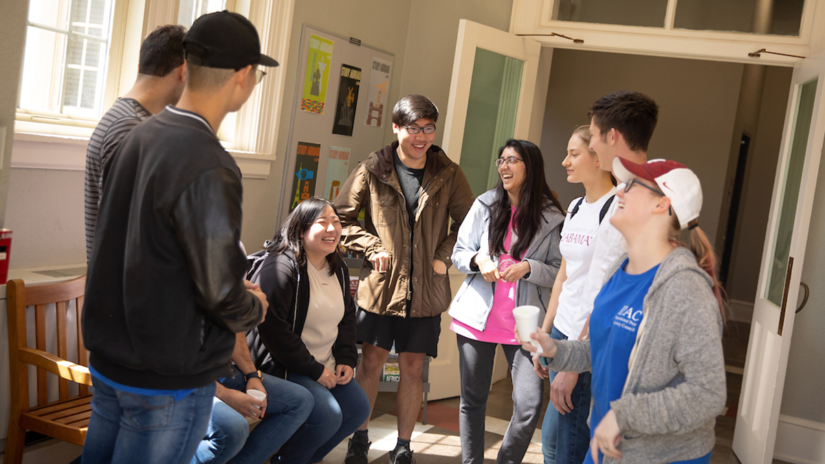 International students laughing together in a hallway